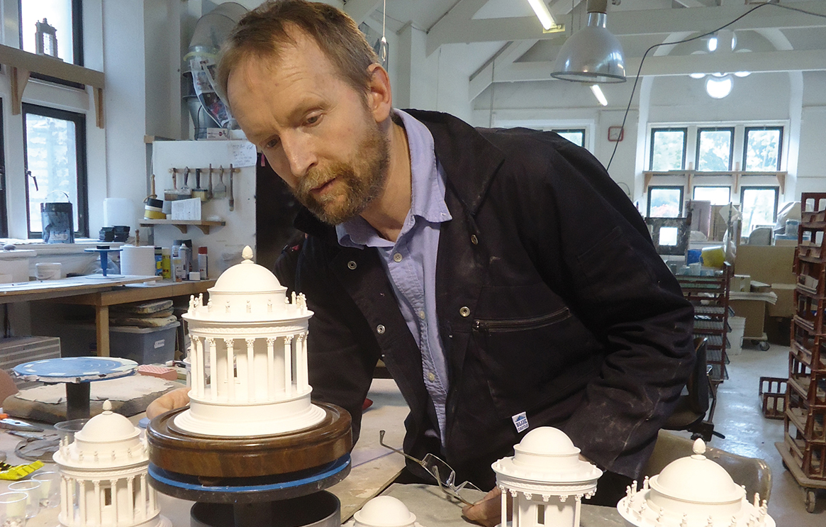Man leaning over a small model of a building