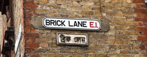 A street sign for 'Brick Lane E1'