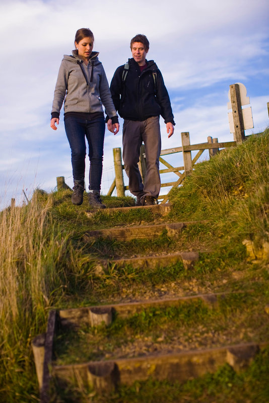 Two people, walkers at the top of steps on the footpath, the Cotswold Way at Coaley Peak.