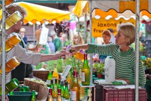 Stroud Farmers Market, stallholders and customers, at a stall selling apple juice and other drinks. A customer having a taste.
