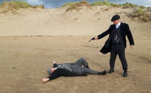 Actors stage a scene on a Peaky Blinders tour in Liverpool on the beach one might points a gun at another lying down