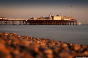 Sunset on Brighton beach. A shingle beach. Waves breaking on the shore. View of Brighton Pier, reaching out into the sea. A historic building, with amusement arcades and funfair rides.