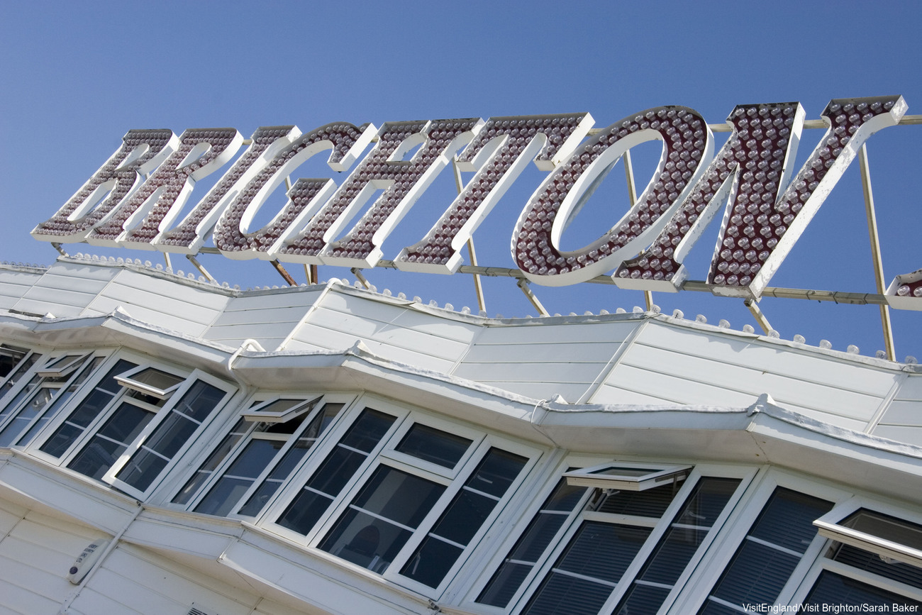 Sign at the entrance to Brighton Pier against blue skies