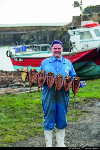 A man in blue overalls holding a rail of Craster Kippers from L. Robson & Sons, in Craster, Northumberland