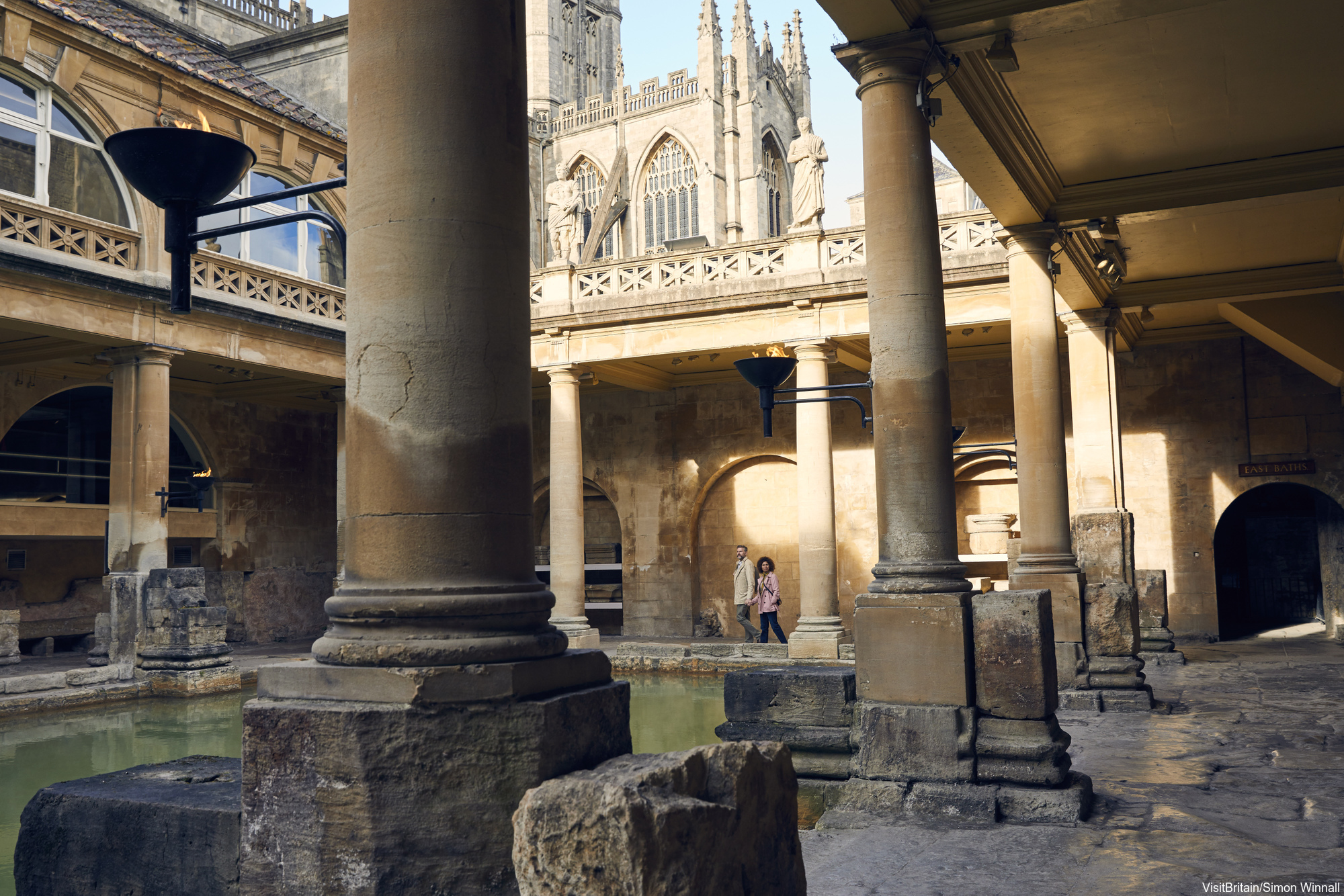 Bath, Somerset, England. A couple, man and woman, walking past columns along the pool at Roman Baths. bath Abbey in the background.