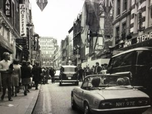 A Lotus Elan rumbles down a blitz-damaged Carnaby Street in the 1960s.