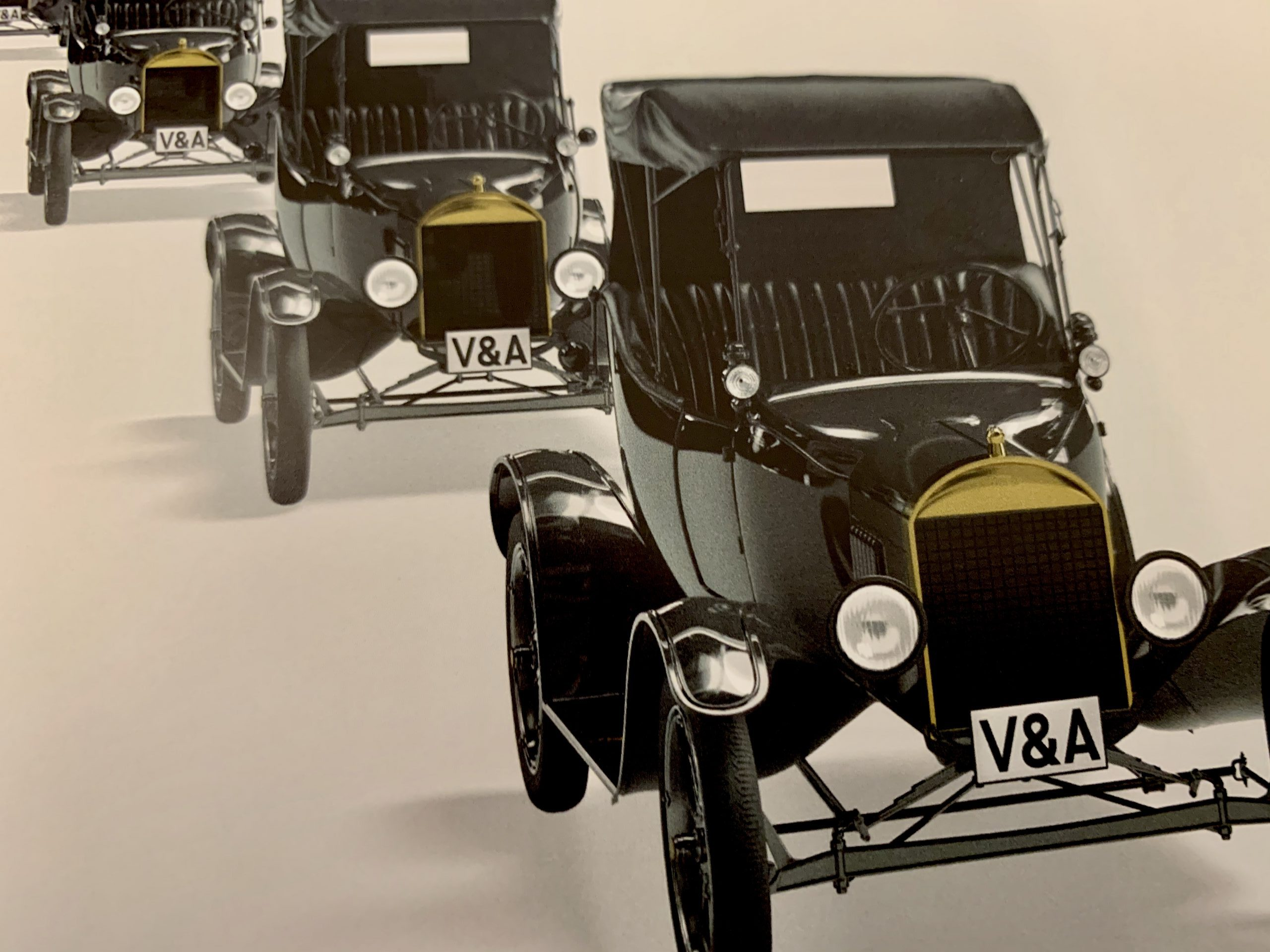 3 black old fashioned cars with numberplates saying V&A