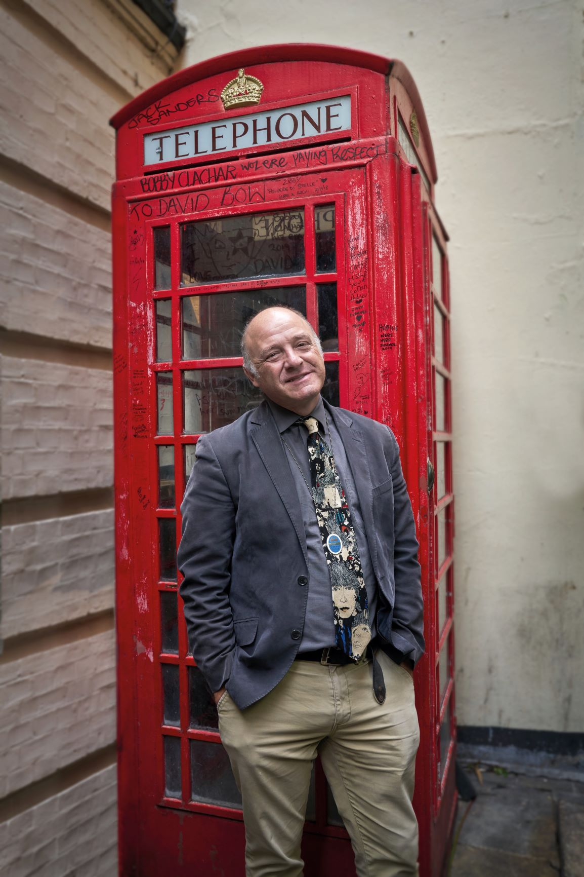 Man standing outside a red telephone box