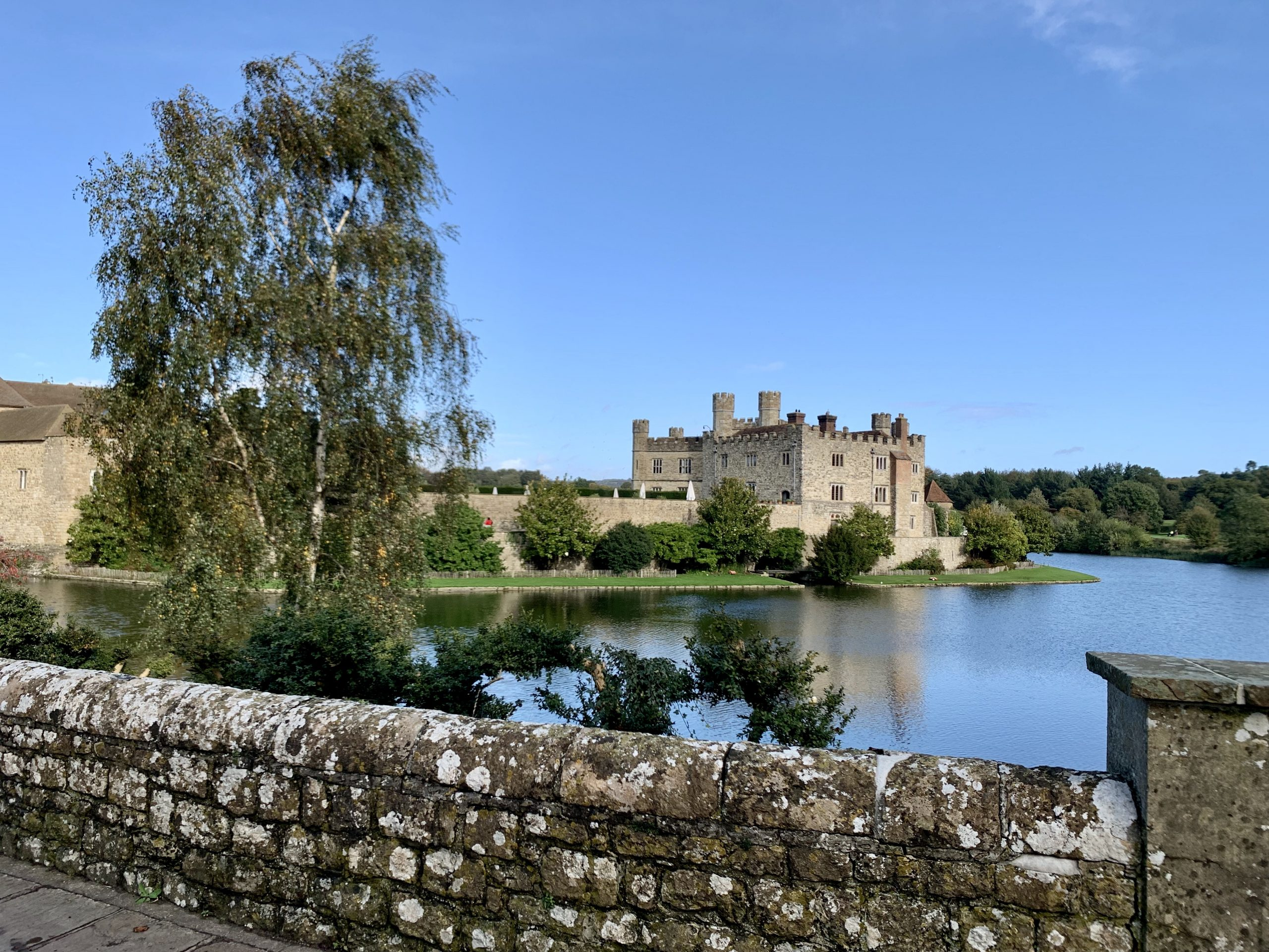 Leeds Castle with a lake and a wall in front