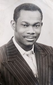 Portrait style photo of a man in a pin striped suit and tie