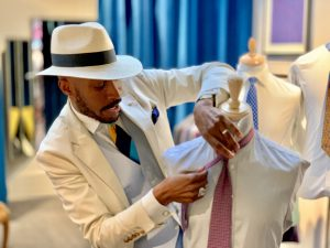 Man in a white suit and hat fixing the tie on a shop manaquin