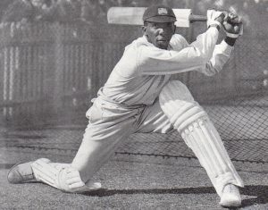 Black man with cricket outfits on striking a ball