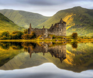 A loch and an old castle with hills behind in the Trossachs in the Highlands tour Scotland